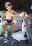 逗人喜爱的与室外的海绵的孩子洗涤的汽车 免版税库存照片