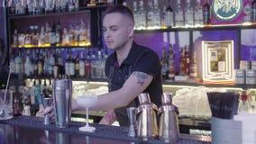 逗人喜爱的专业从量杯的男服务员倾吐的饮料到金属振动器里 影视素材