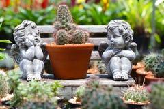 逗人喜爱的丘比特雕象在庭院里 免版税库存照片