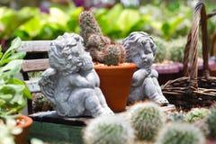 逗人喜爱的丘比特雕象在庭院里 图库摄影