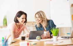 逗人喜爱的两个女性同事在办公室休息 免版税库存照片