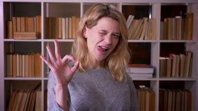 逗人喜爱的中年白肤金发的老师姿态好标志显示成功和满意入照相机在图书馆 股票视频