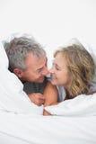 逗人喜爱的中部在鸭绒垫子下的年迈的夫妇 库存图片