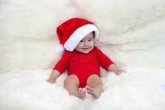 逗人喜爱的五个月微笑与在明亮的软的地毯的圣诞老人帽子的亚裔婴孩 库存照片