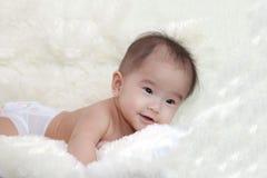 逗人喜爱的五个月笑在软的地毯的亚裔婴孩 免版税图库摄影