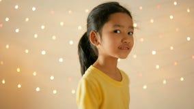 逗人喜爱的亚洲小女孩皮和给在闪烁的轻的背景的花花束 股票视频