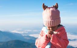 逗人喜爱的亚裔做在祷告的儿童女孩佩带的毛线衣和温暖的帽子被折叠的手在美好的薄雾和山背景中 免版税库存照片