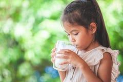 逗人喜爱的亚裔儿童女孩喝从玻璃的牛奶 图库摄影