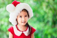 逗人喜爱的亚裔儿童女孩画象圣诞老人红色微笑的 库存图片