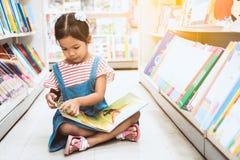逗人喜爱的亚裔儿童女孩精选的书和读一本书在书店 免版税库存照片