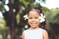 逗人喜爱的亚裔儿童女孩画象有花的在她的耳朵 免版税库存照片