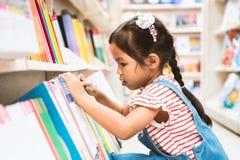 逗人喜爱的亚裔在书架的儿童女孩精选的书在书店 库存图片