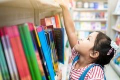 逗人喜爱的亚裔在书架的儿童女孩精选的书在书店 图库摄影