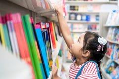 逗人喜爱的亚裔在书架的儿童女孩精选的书在书店 免版税图库摄影