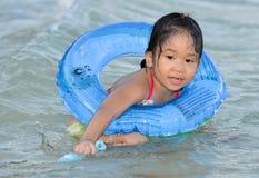 逗人喜爱的亚裔女孩享受游泳。 免版税库存图片