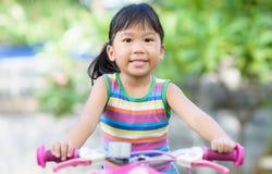 逗人喜爱的亚裔女孩享用骑自行车 库存照片