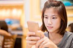 逗人喜爱的亚裔女孩在咖啡馆使用一个手机 免版税库存照片