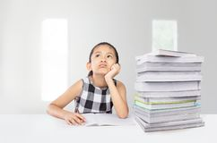 逗人喜爱的亚裔女孩在她的与巨大的堆的研究疲倦了在桌上的课本 免版税库存图片