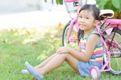 逗人喜爱的亚裔女孩在自行车附近坐 图库摄影