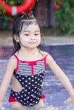 逗人喜爱的亚裔女性小孩孩子,当演奏和飞溅在游泳场时的水 免版税库存图片