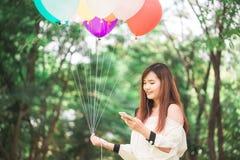 逗人喜爱的亚裔妇女在手机读宜人的正文消息,当坐在公园在温暖的春日时 免版税库存照片