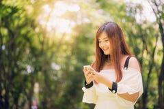 逗人喜爱的亚裔妇女在手机读宜人的正文消息,当坐在公园时 免版税库存照片