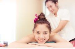 逗人喜爱的亚裔妇女微笑着,当采取温泉时 免版税库存图片