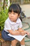 逗人喜爱的亚裔孩子疲倦于家庭作业 免版税库存图片