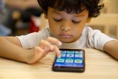 逗人喜爱的亚裔小男孩打在智能手机的一场比赛 库存图片