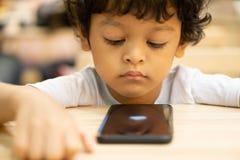 逗人喜爱的亚裔小男孩打在智能手机的一场比赛 免版税库存图片