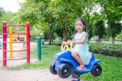逗人喜爱的亚裔泰国小女孩坐在戏剧groun的玩具汽车 免版税图库摄影