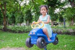 逗人喜爱的亚裔泰国小女孩坐在戏剧groun的玩具汽车 库存图片