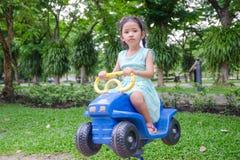逗人喜爱的亚裔泰国小女孩坐在戏剧groun的玩具汽车 库存照片