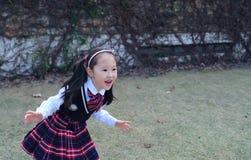 逗人喜爱的亚裔矮小的美丽的女孩在公园跑 免版税图库摄影