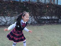逗人喜爱的亚裔矮小的美丽的女孩在公园跑 免版税库存图片