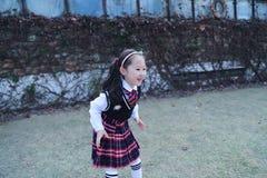 逗人喜爱的亚裔矮小的美丽的女孩在公园跑 库存图片