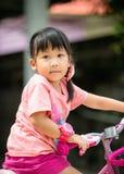 逗人喜爱的亚洲女孩乘驾自行车 库存照片