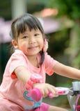 逗人喜爱的亚洲女孩乘驾自行车 免版税库存照片