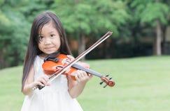 逗人喜爱的亚洲女孩戏剧小提琴 免版税图库摄影