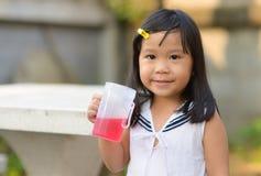 逗人喜爱的亚洲孩子和软饮料 免版税库存照片