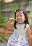 逗人喜爱的亚洲孩子掠过的牙 免版税库存图片