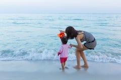 逗人喜爱的享用在海滩的女婴和美丽的母亲 库存图片