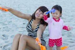 逗人喜爱的享用沙子的女婴和美丽的母亲戏弄 图库摄影