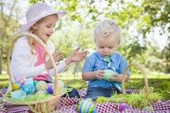 逗人喜爱的享用他们的复活节彩蛋的弟弟和姐妹外面 图库摄影