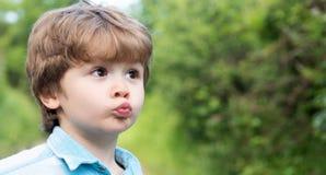 逗人喜爱的亲吻 有亲吻象姿态的孩子 小男孩做了滑稽的嘴唇 E 爱和家庭 惊奇的孩子 库存照片