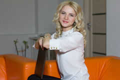 逗人喜爱的企业女孩坐长沙发在办公室 库存照片