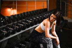 逗人喜爱的体育女孩浅黑肤色的男人在健身房坐在镜子附近在bowties旁边 在训练的断裂 库存照片