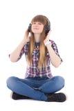 逗人喜爱的作的与头的十几岁的女孩坐的和听的音乐 图库摄影