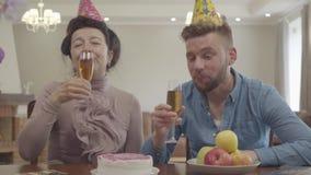 逗人喜爱的使玻璃叮当响的老婆婆和成人孙子在与生日盖帽的桌上坐他们的头 成熟妇女 股票录像