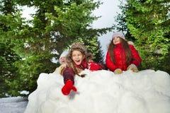 逗人喜爱的使用与朋友的女孩投掷的雪球 库存照片